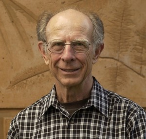 An older man with pale skin stands in front of a wall.  He is wearing spectacles and a plaid shirt.