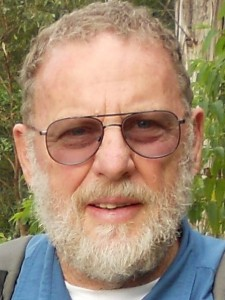 A headshot of an older man with pale skin, sunglasses and a silver beard, in front of greenery.